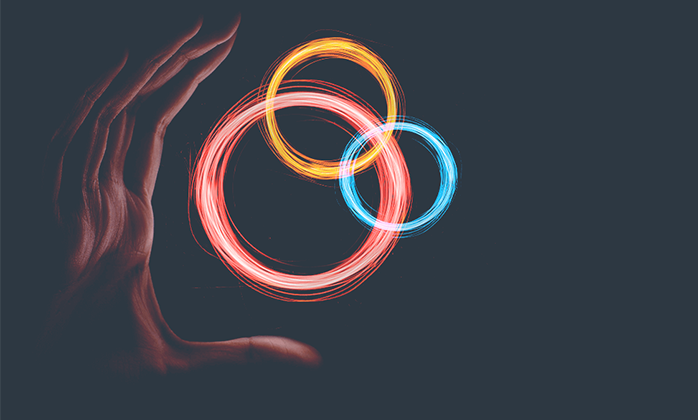 Multi-coloured rings suspended in front of a human hand appearing to hold them