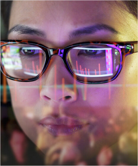 Half-face view of a girl wearing glasses looking at a screen reflecting in her glasses