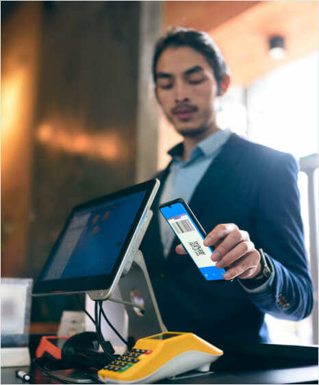 A man using a smartphone to make a payment on a card reading machine