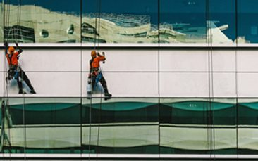 Picture of two people cleaning the facede of a building, valantic object management