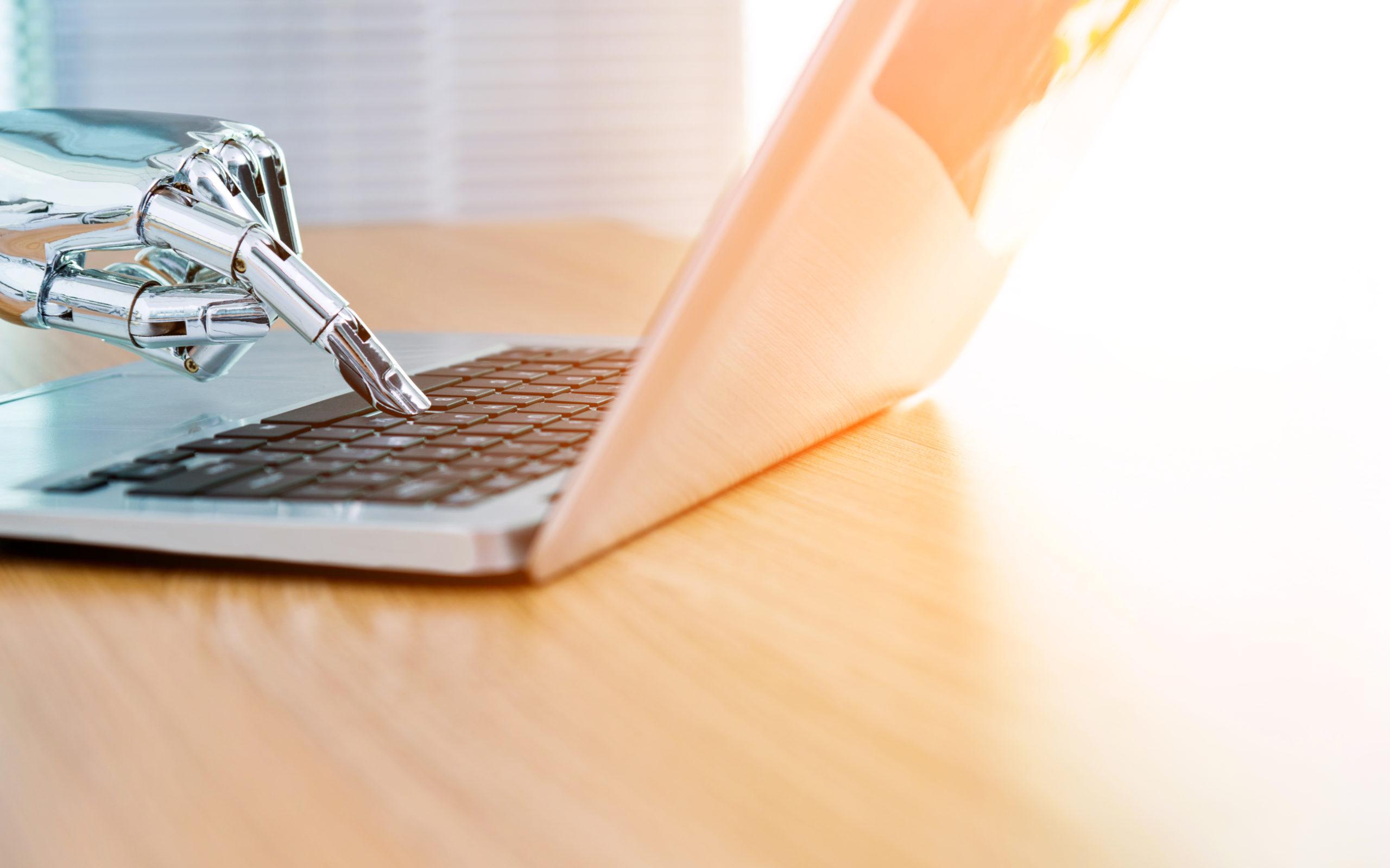 Roboter Hand tippt auf einer Laptop-Tastatur, valantic Whitetaper Chatbots