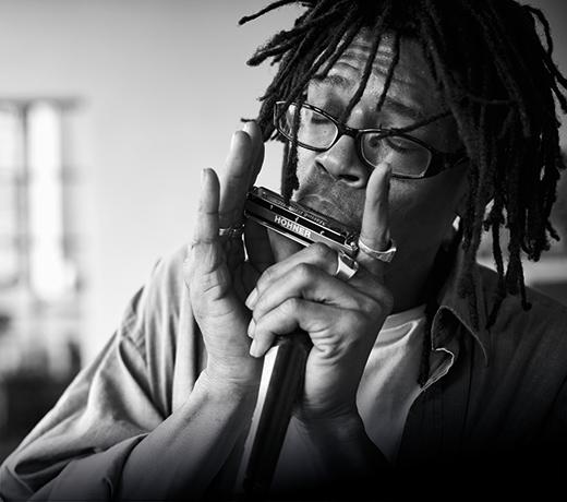 Foto eines Mannes der Mundharmonika spielt