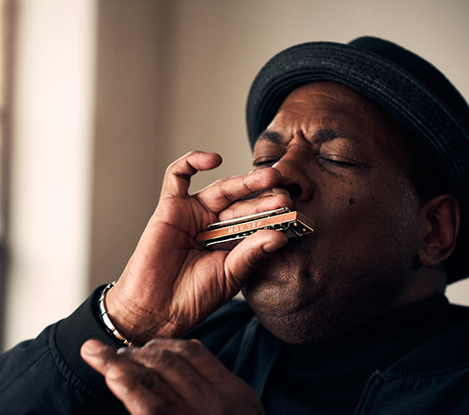Image of musician and music producer keith dunn, playing on a HOHNER harmonica