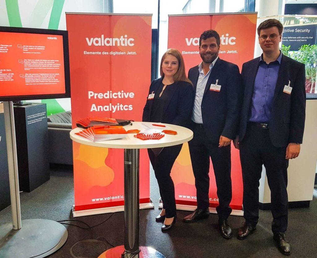 Bild von drei Personen an einem Messestand, Das valantic Team präsentiert als Aussteller und Sponsor auf dem TM1 / Planning Analytics Anwendertag in Stuttgart seine Cognitive Analytics und Predictive Analytics Lösungen.