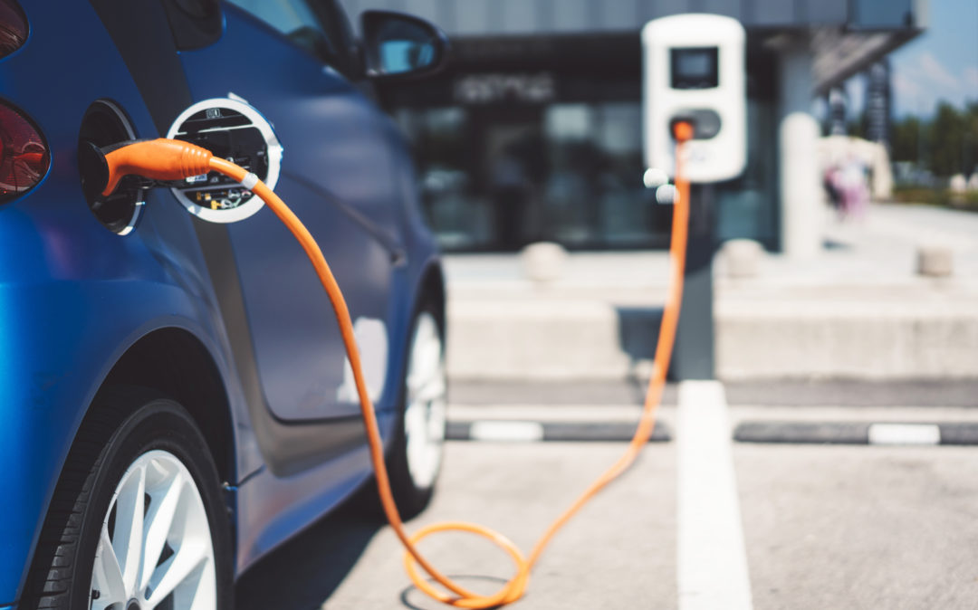 Image of an electric car charging at a charging station, trends in the automotive industry: Sustainability