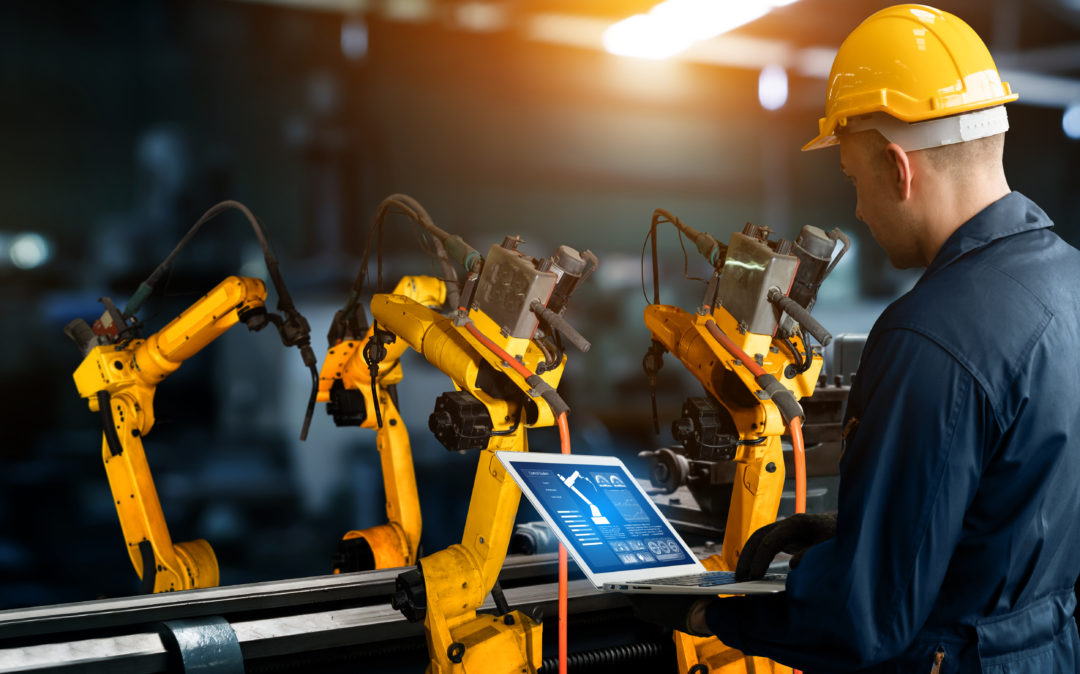 Image of a robotic arm controlled by a man using a laptop, trends in the automotive industry: Smart Industries