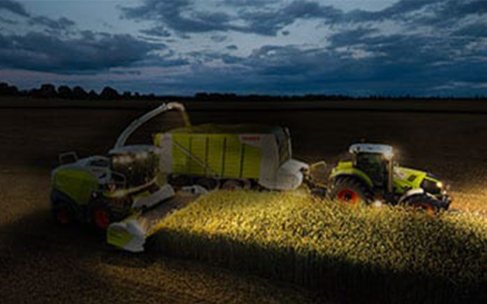 Picture of two harvesting vehicles in night-time operation, valantic Case Study CLAAS