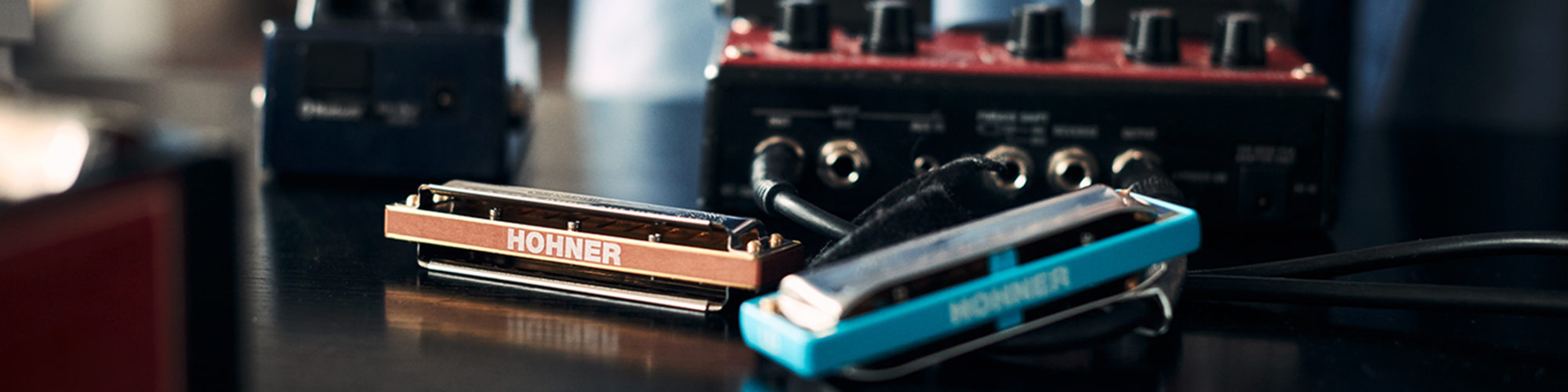 Picture of harmonicas in front of other musical instruments, valantic Case Study Hohner und Sonor