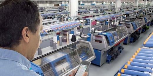 Bild eines Mitarbeiters in der Maschinenhalle der H. Stoll AG & Co. KG mit Handy in der Hand, valantic Case Study Stoll Strickmaschinen