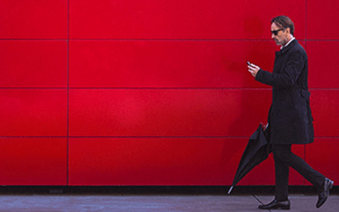Picture of a man with black coat and black umbrella in front of red wall, valantic Case Study E-Plus Telefonica