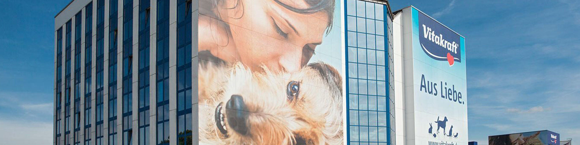 Picture of the Vitakraft company building with a poster of a woman kissing her dog, valantic Case Study Vitakraft