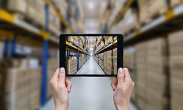 Picture of a tablet in a warehouse full of boxes, valantic logistics management