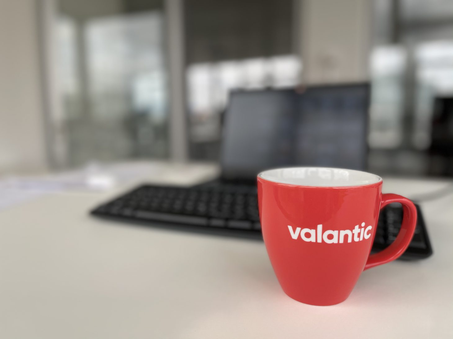 Image of an office desk at the valantic Zurich branch with a view of a coffee cup and laptop
